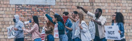 panoramic shot of multicultural people walking near brick wall during protest