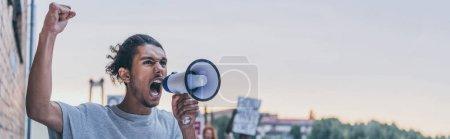 Photo pour Tir panoramique de l'homme américain africain criant tout en retenant le mégaphone - image libre de droit