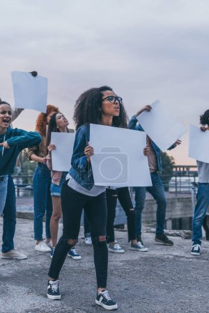 Photo for Emotional multicultural girls screaming and holding blank placards - Royalty Free Image