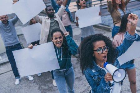 Photo for Emotional multicultural girls screaming and holding blank placards during protest - Royalty Free Image