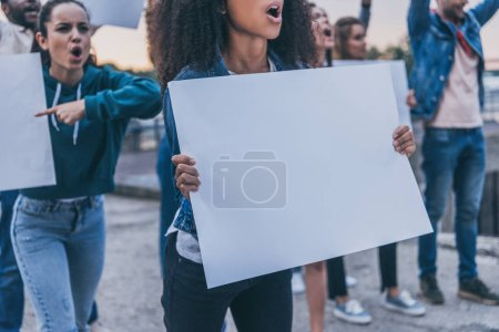 Photo for Cropped view of emotional multicultural girls screaming and holding blank placards during protest - Royalty Free Image