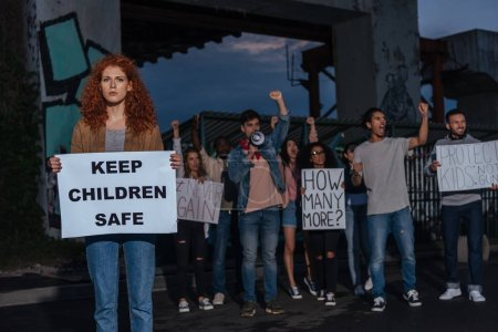 selective focus of redhead girl holding placard with keep children safe lettering near multicultural people on meeting