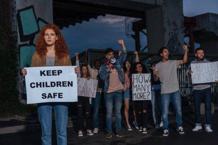 Photo pour Foyer sélectif de la fille rousse tenant l'affiche avec garder les enfants en sécurité lettrage près des personnes multiculturelles sur la réunion - image libre de droit