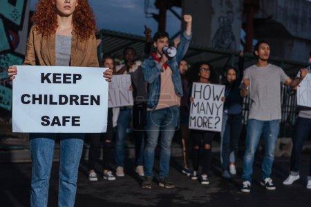 Photo pour Vue recadrée de la fille rousse retenant l'affiche avec garder des enfants en garde à l'enfant en garde à l'aise de lettrage près des personnes multiculturelles sur la réunion - image libre de droit