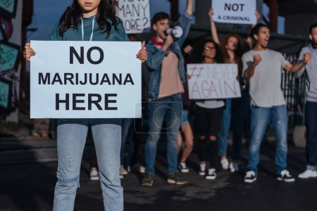 Photo for Cropped view of woman holding placard with no marijuana lettering near screaming multicultural people - Royalty Free Image