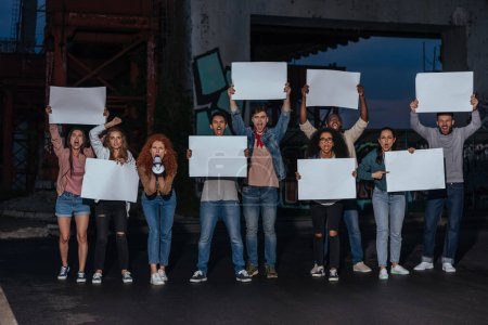 Photo for Emotional multicultural young people holding blank placards on meeting - Royalty Free Image