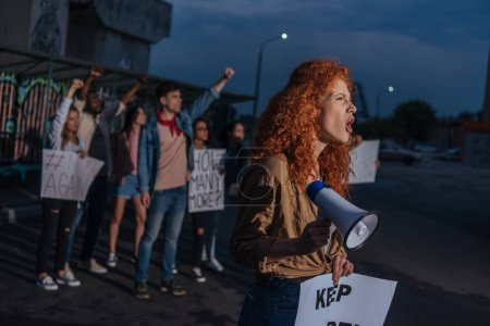 Photo for Selective focus of curly redhead girl holding placard and screaming on meeting - Royalty Free Image