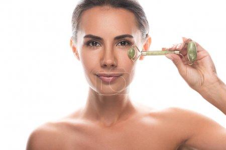 Photo pour Vue de face de jeune femme nue tenant le rouleau de jade facial isolé sur blanc - image libre de droit