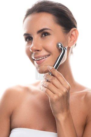 Photo pour Sourire jeune femme en utilisant masseur facial isolé sur blanc - image libre de droit