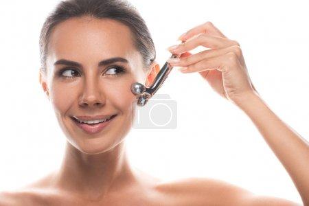Photo pour Vue de face de sourire jeune femme nue en utilisant un masseur facial isolé sur blanc - image libre de droit