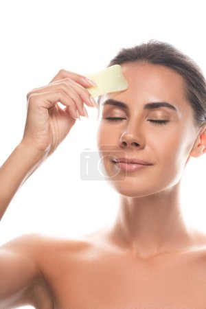 nude young woman using gua sha scraper with closed eyes isolated on white