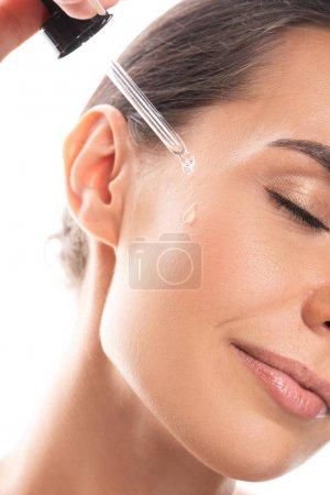 Photo pour Vue recadrée de la jeune femme appliquant du sérum sur le visage isolé sur blanc - image libre de droit