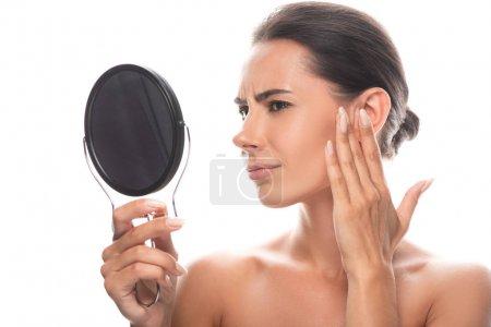 Photo pour Mécontent nu brunette jeune femme regardant dans miroir et touchant visage isolé sur blanc - image libre de droit