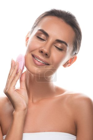 smiling young woman using facial cleansing brush with closed eyes isolated on white