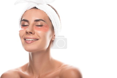 Foto de Nude young woman in cosmetic hair band with eye patches smiling with closed eyes isolated on white - Imagen libre de derechos