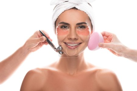 cropped view of cosmetologists using facial cleansing brush and facial massager and smiling woman with eye patches isolated on white
