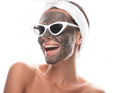 Photo pour Jeune femme nue dans la bande cosmétique de cheveux et des lunettes de soleil avec le masque d'argile sur le visage riant d'isolement sur le blanc - image libre de droit