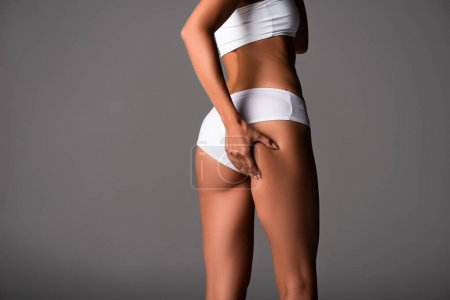 Photo for Cropped view of sexy young woman in white panties touching buttocks on grey - Royalty Free Image