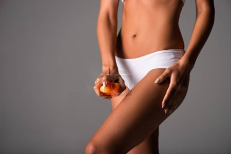 Photo pour Partial view of sexy woman in white panties applying sunscreen on body isolated on grey - image libre de droit