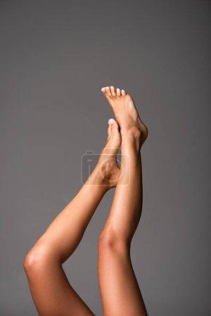 Photo pour Vue partielle de sexy pieds nus jeune femme isolée sur gris - image libre de droit
