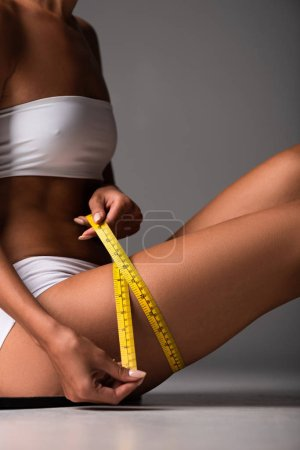 Photo for Partial view of sexy young woman using measuring tape on grey - Royalty Free Image
