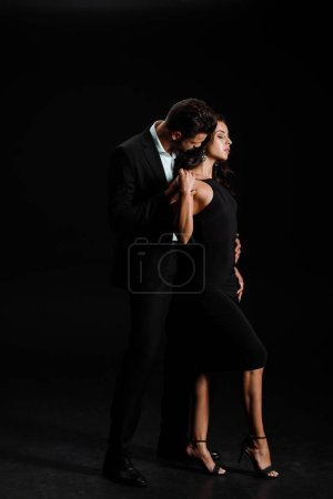 Photo for Man in suit standing and hugging beautiful woman in dress on black - Royalty Free Image