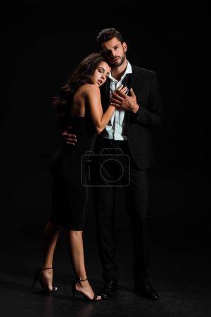 Photo pour Attrayant femme avec les yeux fermés étreignant bel homme barbu tout en se tenant sur noir - image libre de droit