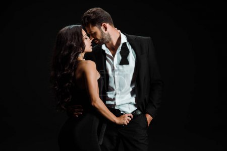 Photo for Passionate girl touching belt of man standing with hand in pocket isolated on black - Royalty Free Image