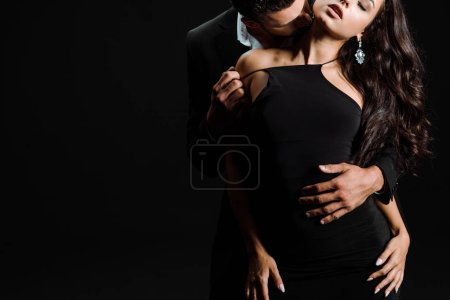 Photo for Cropped view of passionate man kissing woman in dress isolated on black - Royalty Free Image