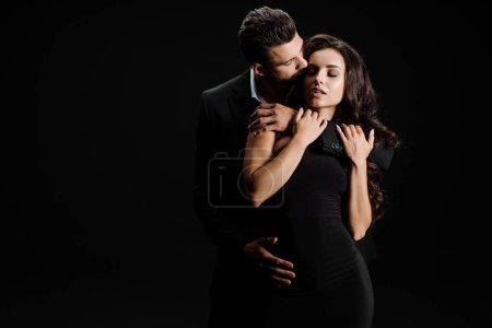 Photo for Handsome man kissing beautiful girl with closed eyes isolated on black - Royalty Free Image
