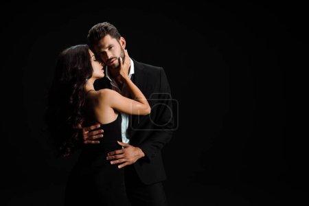 junge attraktive Frau umarmt bärtigen Mann isoliert auf schwarz
