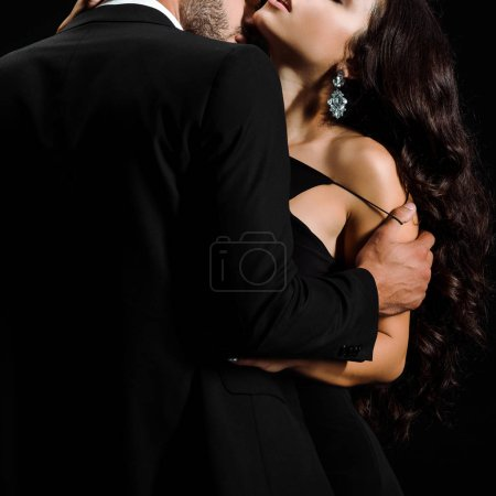 Photo for Cropped view of man undressing young woman isolated on black - Royalty Free Image