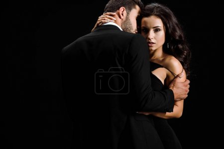 bearded man undressing attractive young woman isolated on black