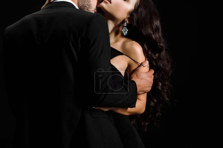 Photo for Cropped view of bearded man undressing young woman isolated on black - Royalty Free Image