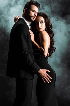 Photo for Bearded man standing and hugging young woman on black with smoke - Royalty Free Image