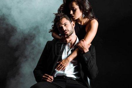Photo pour Passionné jeune femme debout et étreignant bel homme barbu sur noir avec de la fumée - image libre de droit