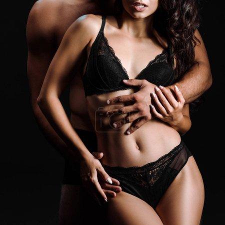 abgeschnittene Ansicht von Mann umarmt sexy Mädchen in Unterwäsche isoliert auf schwarz