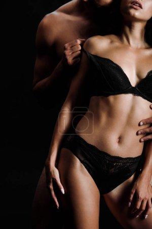 Photo pour Vue recadrée de l'homme musculaire déshabillant la fille sexy dans des sous-vêtements isolés sur le noir - image libre de droit