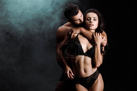 Photo for Handsome bearded man looking at attractive girl in lace underwear on black with smoke - Royalty Free Image
