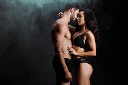 Photo for Young woman hugging handsome and shirtless man on black with smoke - Royalty Free Image