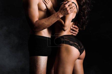 Photo pour Vue recadrée de l'homme torse nu touchant femme sexy en dentelle sous-vêtements sur noir avec de la fumée - image libre de droit