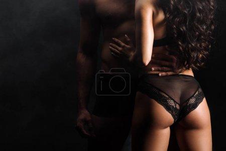 vue recadrée de l'homme debout avec femme sexy sur noir avec de la fumée