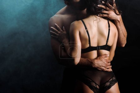 cropped view of woman in underwear hugging shirtless man on black with smoke