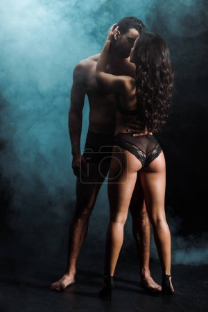 Photo for Sexy young woman in underwear hugging shirtless man on black with smoke - Royalty Free Image