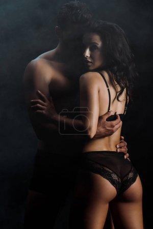 Photo pour Fille sexy dans la lingerie de dentelle étreignant l'homme musculaire sur le noir avec la fumée - image libre de droit