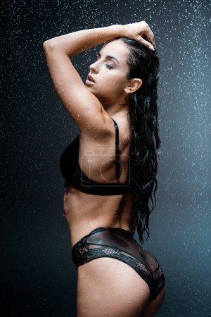 Photo pour Femme passionnée avec les yeux fermés touchant les cheveux tout en se tenant sous les gouttes de pluie sur noir - image libre de droit