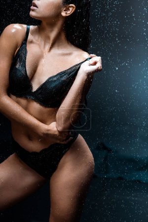 cropped view of sexy woman touching lace bra while standing under raindrops on black