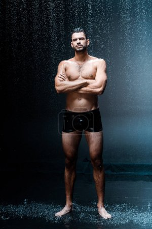 wet handsome man looking at camera while standing with crossed arms under raindrops on black