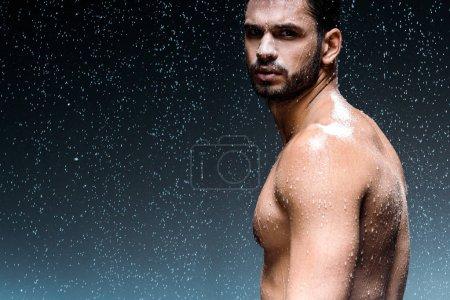 Photo pour Homme humide regardant caméra tout en se tenant sous les gouttes de pluie sur noir - image libre de droit