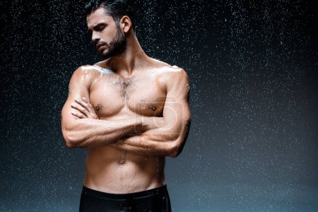 Photo for Handsome wet man standing with crossed arms under raindrops on black - Royalty Free Image